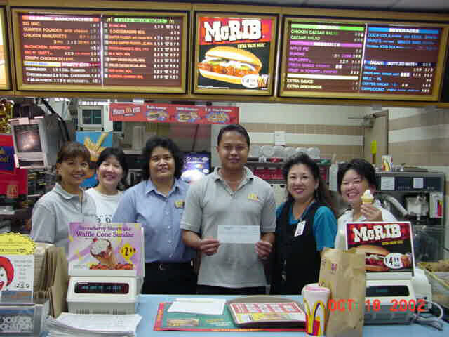 KKHS Staff Smiles While McDonalds Owner, Grelyn Rosario Holds Check At the End