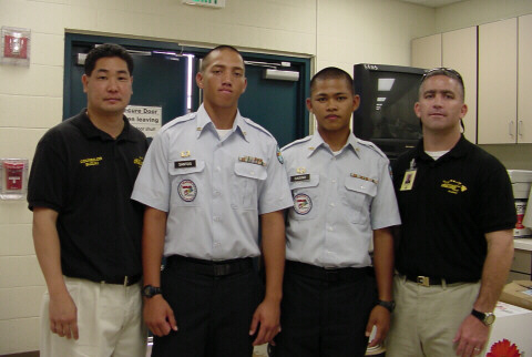 Cpt. Slavins, Leader Branden Suzuki, & 2 students in the Youth Challenge Program in KKHS library workroom, Oct. 7, 2003.